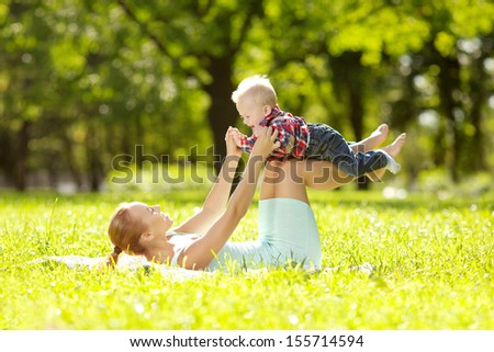 Cute little baby in summer  park with mother  on the grass. Sweet baby and mom  outdoors. Smiling emotional kid with mum on a walk. Smile of a child #155714594