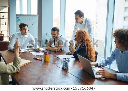 A business consultant explaining his ideas and methods to a group of corporate employees. A meeting at the conference hall. Workers learning new techniques. Atmosphere of growth and success. #1557166847