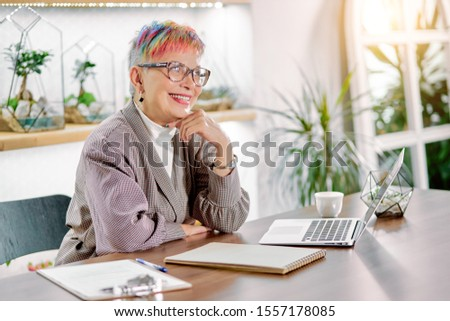Portrait of well-favoured woman involved in business work smile, wearing blazer, glasses, short colorful hair. Isolated in light office, plants background #1557178085