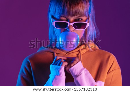 Stylish pretty young 20s fashion teen girl model wear glasses blowing bubble gum winking looking at camera stand at purple studio background, igen teenager in trendy light 80s 90s concept, portrait #1557182318