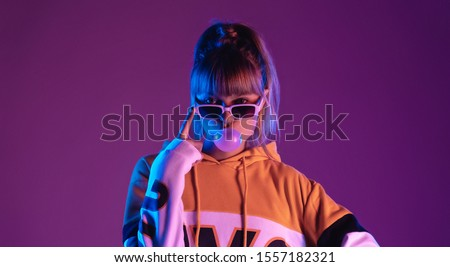 Pretty young 20s fashion teen girl model wear glasses blowing bubble gum looking at camera standing at purple studio background, igen teenager in trendy stylish night glow 80s 90s concept, portrait #1557182321