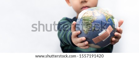 Closeup banner of a cute little asian boy a new generation presenting a damage globe full of bandages. Global warming, Climate change, Environmental problems. World pollution, Earth day, April 22. Royalty-Free Stock Photo #1557191420