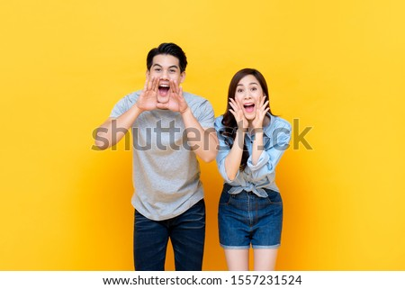 Young lovely asian couple yelling with hands cup around mouths isolated on yellow studio background #1557231524