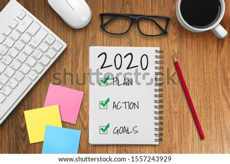 New Year Resolution Goal List 2020 - Business office desk with notebook written in handwriting about plan listing of new year goals and resolutions setting. Change and determination concept. #1557243929