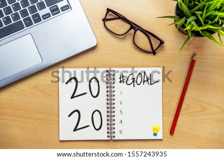 New Year Resolution Goal List 2020 - Business office desk with notebook written in handwriting about plan listing of new year goals and resolutions setting. Change and determination concept. #1557243935