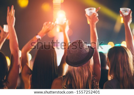Back view of female friends drinking beer and dancing at music festival #1557252401
