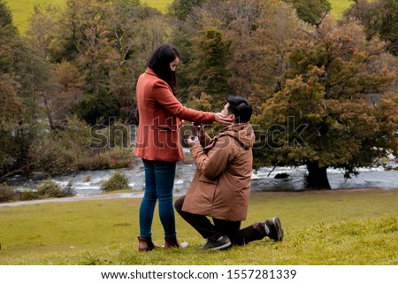 Will you marry me traditional kneeling proposal, happy attractive Asian couple fall in love make proposal to get married engagement with diamond ring in Autumn landscape, beautiful woman crying tears  #1557281339
