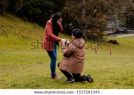 Will you marry me traditional kneeling proposal, happy attractive Asian couple fall in love make proposal to get married engagement with diamond ring in Autumn landscape, beautiful woman crying tears  #1557281345