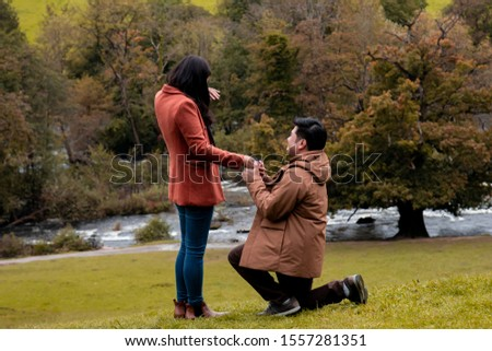 Will you marry me traditional kneeling proposal, happy attractive Asian couple fall in love make proposal to get married engagement with diamond ring in Autumn landscape, beautiful woman crying tears  #1557281351