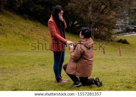 Will you marry me traditional kneeling proposal, happy attractive Asian couple fall in love make proposal to get married engagement with diamond ring in Autumn landscape, beautiful woman crying tears  #1557281357