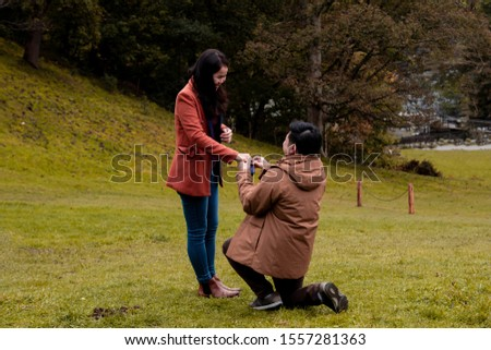 Will you marry me traditional kneeling proposal, happy attractive Asian couple fall in love make proposal to get married engagement with diamond ring in Autumn landscape, beautiful woman crying tears  #1557281363