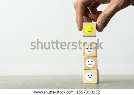 Conceptual the customer responded to the survey. The Businessman hand choose happy face smile icon on top. Depicts that customer is very satisfied. Service experience satisfaction concept. #1557350132