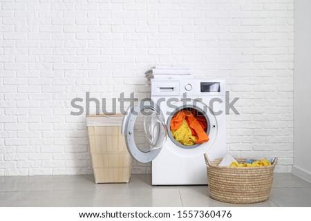 Modern washing machine with laundry near white brick wall #1557360476