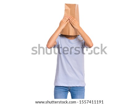 Portrait of teen girl with paper bag over her head with hands on face covering eyes, isolated on white background. Shy child pulling paper bag over her head close eyes with palms. See no evil concept. #1557411191