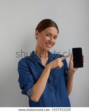 Isolated Young positive green eyes brunette woman ticked back hair in blue jeans shirt dress promote smartphone holds in hand and shows point finger to camera looks to camera on white wall background  #1557415220