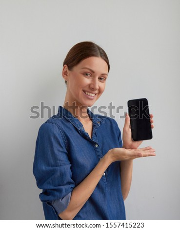 Isolated Young positive green eyes brunette woman ticked back hair in blue jeans shirt dress promote smartphone holds in hand and shows to camera looks to camera on white wall background  #1557415223