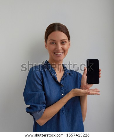Isolated Young positive green eyes brunette woman ticked back hair in blue jeans shirt dress promote smartphone holds in hand and shows to camera looks to camera on white wall background  #1557415226
