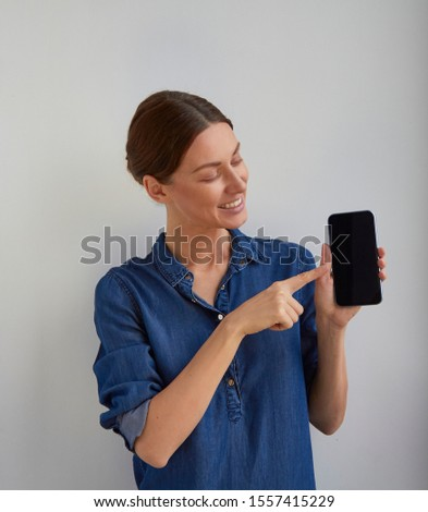 Isolated Young positive green eyes brunette woman ticked back hair in blue jeans shirt dress promote smartphone holds in hand and shows point finger to camera looks to camera on white wall background  #1557415229