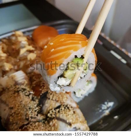 Macro photo Asian food sushi rolls. Stock photo eat sushi with chopsticks