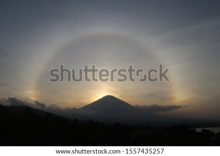 A 22 ° halo is an optical phenomenon that belongs to the family of ice-crystal halos. Halo effect before sunset over Agung volcano in Bali, Indonesia. Frozen ice crystals in the atmosphere. #1557435257