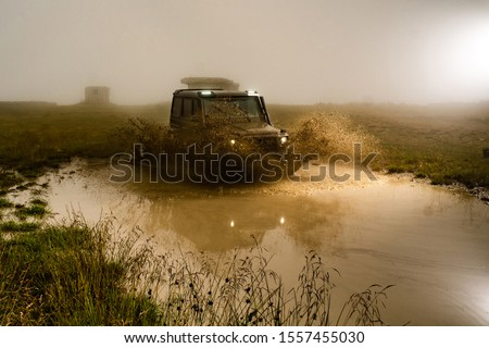 Mud and water splash in off-road racing. Off road car. Beautiful nature. Truck car wheel on offroad steppe adventure trail #1557455030