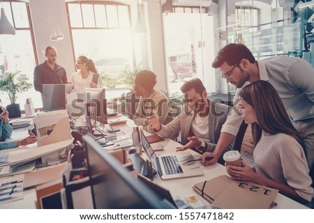 Group of young modern people in smart casual wear communicating and using modern technologies while working in the office #1557471842
