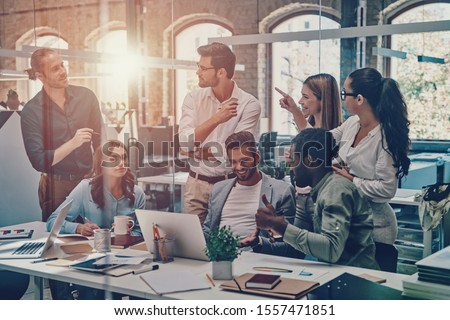 Group of young modern people in smart casual wear communicating and using modern technologies while working in the office #1557471851