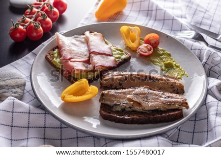Homemade smoked herring and schwarzwald ham sandwiches with rye bread on light grey plate, top view  #1557480017