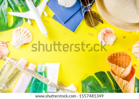 Travel and vacation flatlay concept. Summer bright colorful background with hat, sunglasses, plane,  passport, tropical leaves, travel cosmetics kit, seashells, copy space top view banner #1557481349