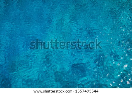 Blue ripped water in swimming pool. Surface of blue swimming pool, background of water in swimming pool. Water swimming pool texture.  #1557493544