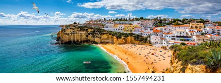 View of Carvoeiro fishing village with beautiful beach, Algarve, Portugal. View of beach in Carvoeiro town with colorful houses on coast of Portugal. The village Carvoeiro in the Algarve Portugal. #1557494231