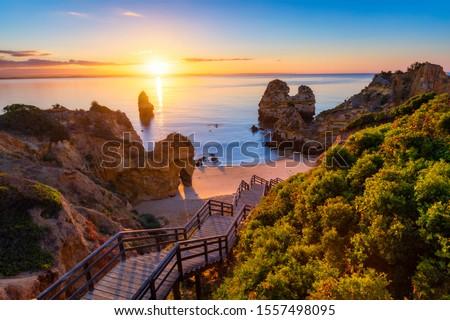 Sunrise at Camilo beach in Lagos, Algarve, Portugal. Wooden footbridge to the beach Praia do Camilo, Portugal. Picturesque view of Praia do Camilo beach in Lagos, Algarve region, Portugal. #1557498095