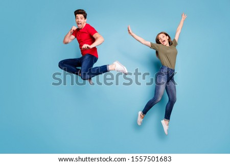 Full size photo of funky crazy two people spouses students man fight kick hands fists woman jump fool raise arms wear green red t-shirt denim jeans sneakers isolated blue color background #1557501683