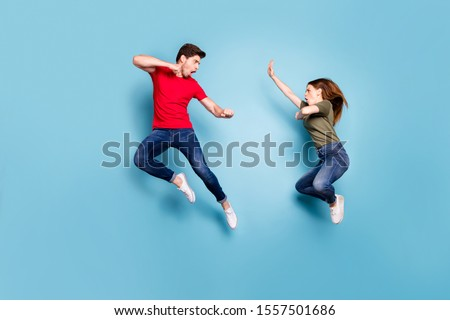 Full size photo of crazy mad two people married man woman jump train kickboxing exercise kick decide who is best wear green red t-shirt denim jeans isolaed over blue color background #1557501686