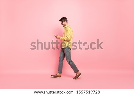 Full size profile photo of handsome guy going street finished working week typing girlfriend sms telephone wear specs striped shirt pants isolated pink color background
