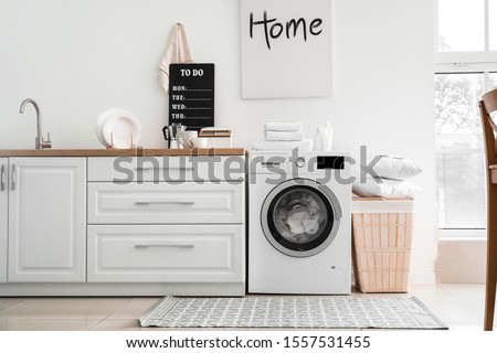 Interior of kitchen with modern washing machine Royalty-Free Stock Photo #1557531455