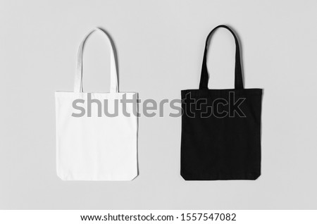White and black tote bags mockup on a grey background. Royalty-Free Stock Photo #1557547082
