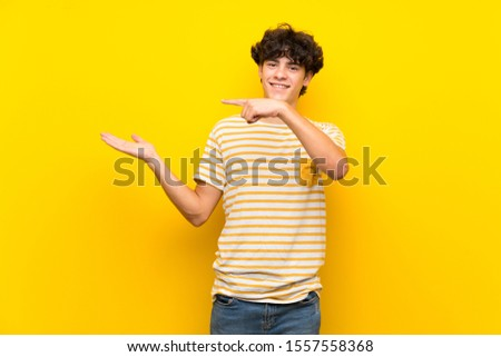 Young man over isolated yellow wall holding copyspace imaginary on the palm to insert an ad #1557558368