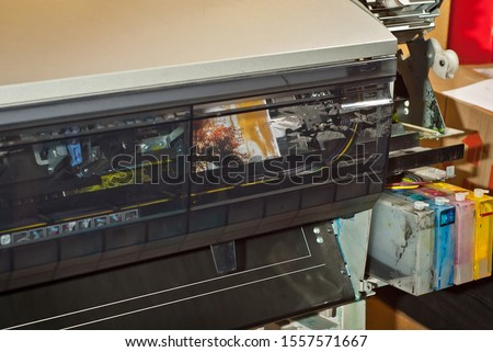 Old broken printer in workshop. The concept of cleaning and calibrating printers. Sunset, tent and green grass in the photo. Picturesque nature photo printed on printing equipment. #1557571667