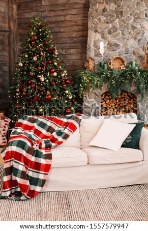 Christmas cozy interior. Christmas tree and a fireplace decorated with garlands in a bright wooden room. Chalet. House in the Alps. #1557579947