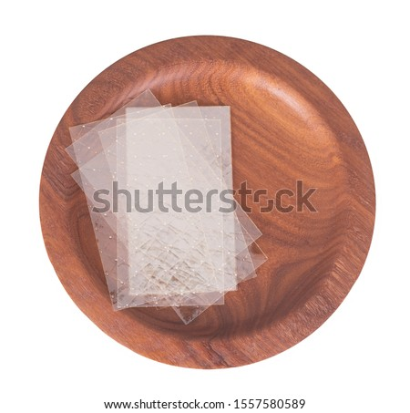 Sheets of colourless gelatin aka gelatine leaves on a wooden plate isolated on white. Food ingredient. Royalty-Free Stock Photo #1557580589