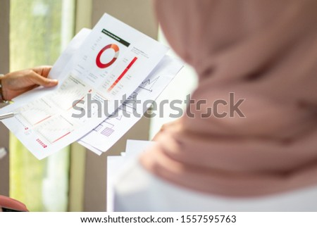 Close-up of a woman holding a document. Financial graph, pie graph #1557595763