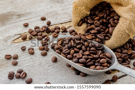 Dark roasted coffee beans with scoop on wooden background #1557599090