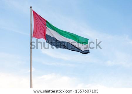 UAE flag waving in the blue bright sky, national symbol of UAE Royalty-Free Stock Photo #1557607103