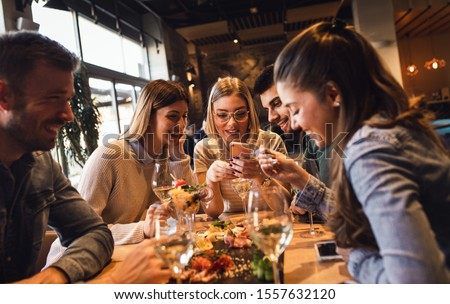 Group of young friends having fun in restaurant, talking and laughing while dining at table. #1557632120