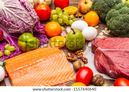 Trending paleo/pegan diet. Healthy balanced food concept. Set of fresh products, raw meat, salmon, vegetables and fruits. Old wooden boards background #1557640640