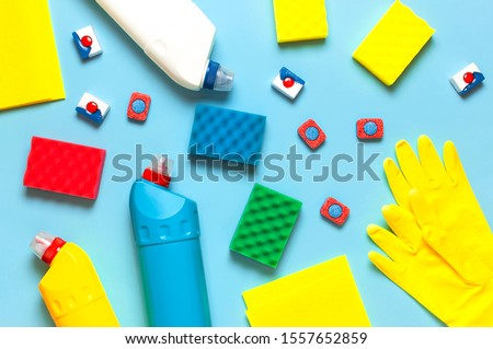 House cleaning concept. Household chemicals, disinfectant, bleach, antibacterial gel, yellow rubber gloves, sponge, rags, dishwasher tablets on blue background. Flat lay top view. Cleaning accessories #1557652859