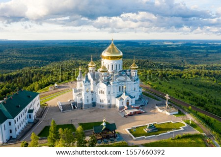 Aerial view of Belogorsky Monastery - russian orthodox church cathedral building with golden domes on hill top among green forest landscape at sunset. Belaya Gora, Perm krai, Russia Royalty-Free Stock Photo #1557660392