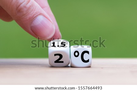 """Symbol for limiting global warming. Hand turns a dice and changes the expression """"2°C"""" to """"1.5°C"""", or vice versa. #1557664493"""