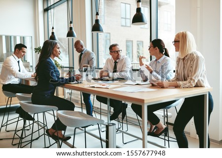 Focused group of diverse businesspeople discussing paperwork together during a meeting around a table in a modern office #1557677948